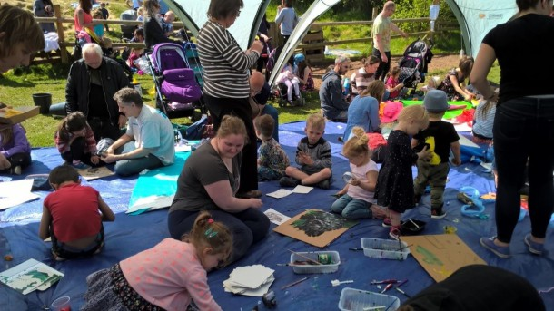 Young volunteer Megan in the centre of a busy craft tent facilitating messy play for children at busy BAPP playday at Bath City Farm.